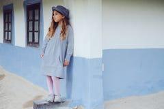 Muchacha adolescente en ropa casual y sombrero azul cerca por la casa del pueblo Foto de archivo libre de regalías