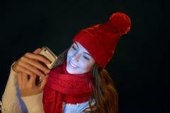 Muchacha adolescente en sombrero caliente con el teléfono elegante Foto de archivo
