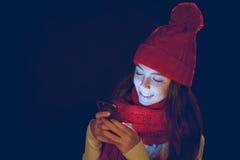 Muchacha adolescente en sombrero caliente con el teléfono elegante Fotos de archivo