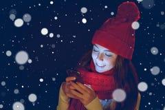 Muchacha adolescente en sombrero caliente con el teléfono elegante Fotos de archivo libres de regalías