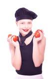 Muchacha adolescente en sombrero del cocinero con los tomates Imagenes de archivo