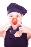 Muchacha adolescente en sombrero del cocinero con los tomates Imágenes de archivo libres de regalías