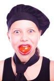 Muchacha adolescente en sombrero del cocinero con los tomates Foto de archivo