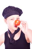 Muchacha adolescente en sombrero del cocinero con los tomates Fotos de archivo libres de regalías
