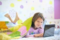 Muchacha adolescente en su cama que mira en la computadora portátil Fotos de archivo libres de regalías