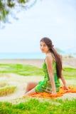 Muchacha adolescente en sundress verdes en la playa que mira sobre hombro Imagenes de archivo