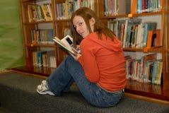 Muchacha adolescente en teléfono celular de ocultación de la biblioteca 2 Imágenes de archivo libres de regalías