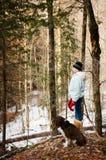 Muchacha adolescente en un bosque con su perro Fotografía de archivo libre de regalías