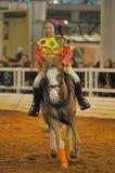 Muchacha adolescente en un bufón del traje en un caballo Fotografía de archivo