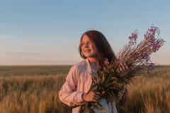 Muchacha adolescente en un campo con las flores Foto de archivo