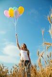 Muchacha adolescente en un campo de trigo con los globos Fotografía de archivo libre de regalías