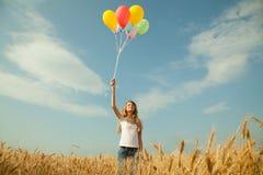 Muchacha adolescente en un campo de trigo con los globos Imágenes de archivo libres de regalías