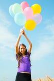 Muchacha adolescente en un campo de trigo con los globos Fotos de archivo