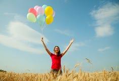Muchacha adolescente en un campo de trigo con los globos coloridos Imagen de archivo