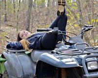 Muchacha adolescente en un coche de cuatro ruedas Fotografía de archivo