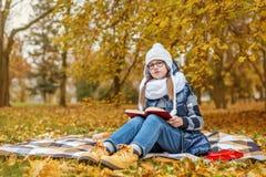 muchacha adolescente en un parque frío que estudia un libro y que se sienta en una manta en una tierra fría Fotografía de archivo libre de regalías