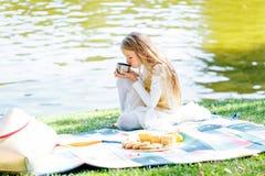 Muchacha adolescente en un parque que bebe sobre fondo del agua Imagen de archivo libre de regalías