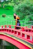 Muchacha adolescente en un puente japonés o del chino rojo de Bhuddist del templo Imágenes de archivo libres de regalías