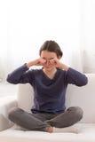Muchacha adolescente en un sofá que la frota ojos Imagenes de archivo