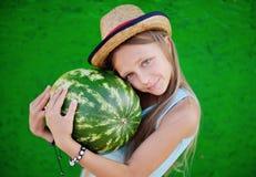 Muchacha adolescente en un sombrero de paja que sostiene una sandía grande Teenag de la muchacha Imagen de archivo