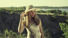 Muchacha adolescente en un sombrero que presenta contra el río almacen de metraje de vídeo