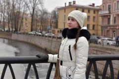 Muchacha adolescente en una capa y un sombrero blancos Foto de archivo