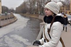 Muchacha adolescente en una capa y un sombrero blancos Fotos de archivo