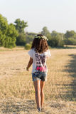 Muchacha adolescente en una guirnalda del walketh de las margaritas en campo Imágenes de archivo libres de regalías