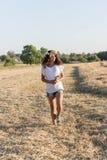 Muchacha adolescente en una guirnalda del walketh de las margaritas en campo Foto de archivo