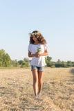 Muchacha adolescente en una guirnalda del walketh de las margaritas en campo Foto de archivo libre de regalías