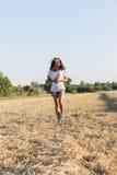 Muchacha adolescente en una guirnalda del walketh de las margaritas en campo Fotos de archivo libres de regalías