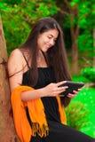 Muchacha adolescente en vestido negro al aire libre usando la tableta Fotos de archivo libres de regalías
