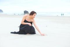 Muchacha adolescente en vestido que se arrodilla, escribiendo en arena en la playa Fotos de archivo libres de regalías