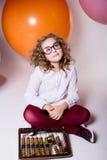 Muchacha adolescente en vidrios con el ábaco de madera en el fondo del lar Fotos de archivo