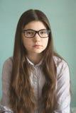 Muchacha adolescente en vidrios con el pelo marrón largo Foto de archivo