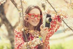 Muchacha adolescente en vidrios con la cámara del vintage cerca del árbol del flor Fotos de archivo libres de regalías
