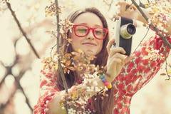 Muchacha adolescente en vidrios con la cámara del vintage cerca del árbol del flor Imagenes de archivo