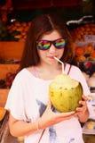 Muchacha adolescente en vidrios de sol con el coco y la paja Imagen de archivo