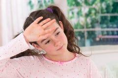 Muchacha adolescente enferma con el dolor de cabeza que lleva a cabo su cabeza Fotos de archivo libres de regalías