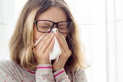Muchacha adolescente enferma con el pañuelo en casa Fotos de archivo