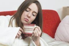 Muchacha adolescente enferma con la taza de té Fotos de archivo