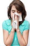 Muchacha adolescente enferma que usa el tejido en el fondo blanco Imagen de archivo libre de regalías