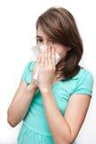 Muchacha adolescente enferma que usa el tejido en el fondo blanco Foto de archivo