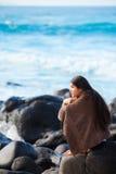 Muchacha adolescente envuelta en la toalla que se sienta en la playa rocosa Fotografía de archivo libre de regalías