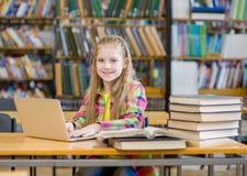 Muchacha adolescente feliz con el ordenador portátil en biblioteca Fotos de archivo libres de regalías