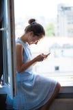 Muchacha adolescente feliz con el teléfono elegante Foto de archivo