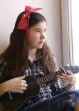 Muchacha adolescente feliz con la guitarra del ukelele en camisa comprobada y vaqueros que juegan mirada en la ventana Fotos de archivo libres de regalías