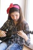 Muchacha adolescente feliz con la guitarra del ukelele en jugar comprobado de la camisa y de los vaqueros Fotos de archivo