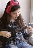 Muchacha adolescente feliz con la guitarra del ukelele en jugar comprobado de la camisa y de los vaqueros Imágenes de archivo libres de regalías