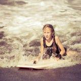 Muchacha adolescente feliz con la tabla hawaiana en la playa Foto de archivo